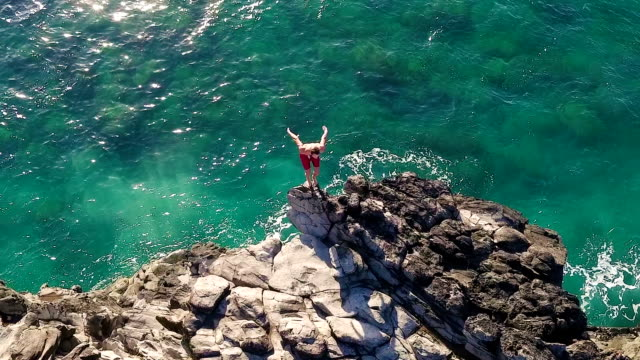 Summer Extreme Sports Cliff Jumping Outdoor Lifestyle Aerial View of Cliff Jumping into Ocean. Young Man Jumps off Cliff Into Blue Ocean. Summer Extreme Sports Outdoor Lifestyle. cliff jumping stock videos & royalty-free footage