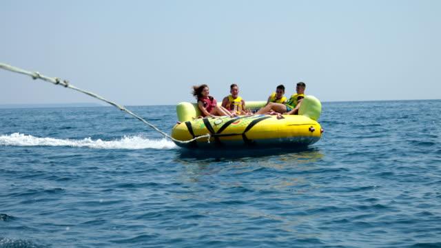 stockvideo's en b-roll-footage met de pret van de zomer. vier vrienden genieten van een opblaasbare buis rijden op zee - opblaasband