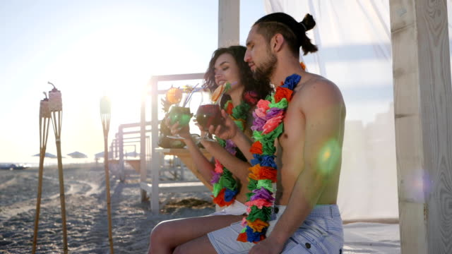 summer holiday on tropical island, happy guy and girl on beach party an exotic vacation, woman with male drink alcohol cocktail video