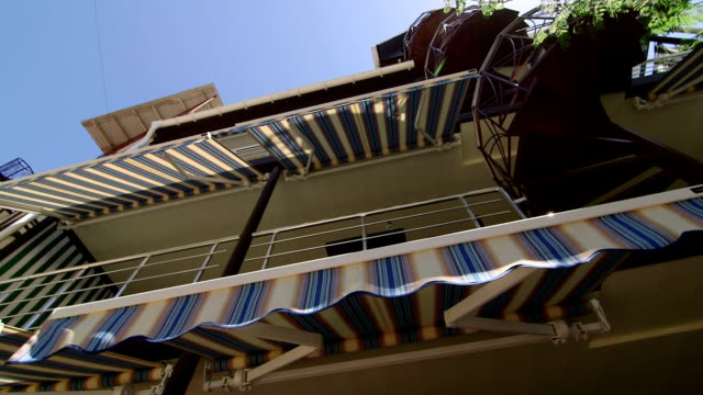 Summer hotel exterior with retractable striped awnings and spiral staircase video