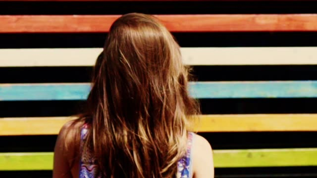 Summer in the city. Colorful stripy background and woman