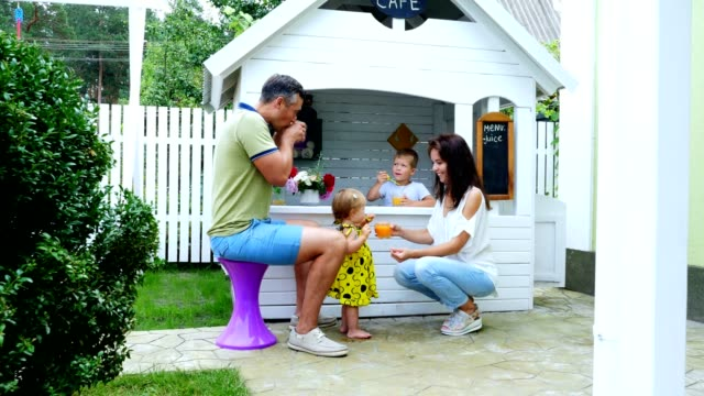 summer, in the garden, parents play with young children, a girl and a boy, in a cafe, in a children's play house, treat children with freshly squeezed fruit juices, drink juices video