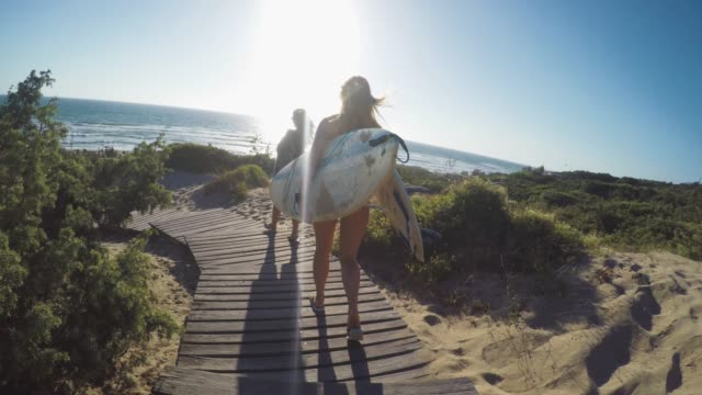 Summer is here: POV surfer girl in action Surfing pov with action camera: surfer girls point of view video, walking to the sea with surfboards angle stock videos & royalty-free footage