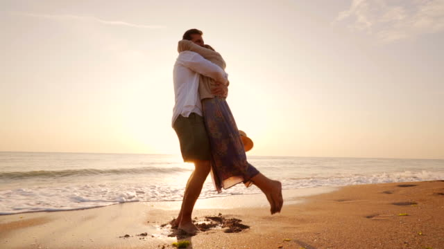 Summer love. Happy young couple having romantic moments at the beach. They are enjoying a beautiful vacation in two. falling in love stock videos & royalty-free footage