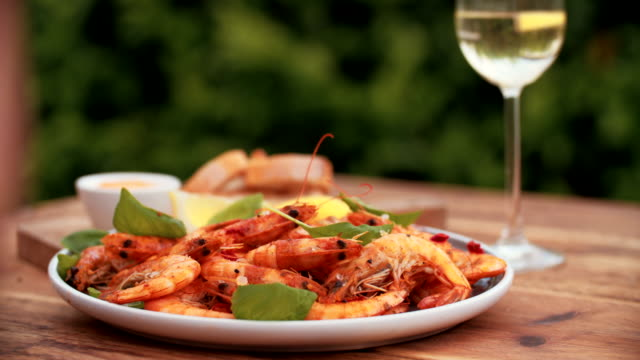 Summer meal of barbecued prawns and white wine outdoors video