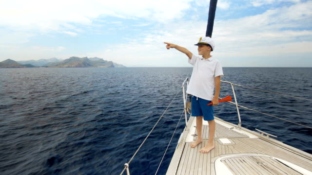 vídeos de stock e filmes b-roll de summer picture. a happy boy in a cap is standing on the yacht and counting the number of yachts that went to sea. racing of sailing yachts - regata