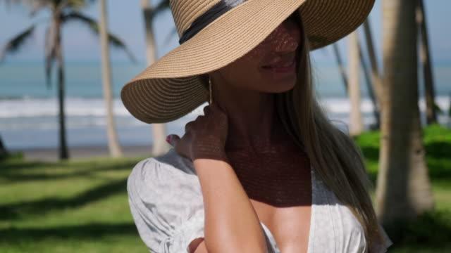 sommerporträt von verführerischen und flirty blondine in tropen - strohhut stock-videos und b-roll-filmmaterial