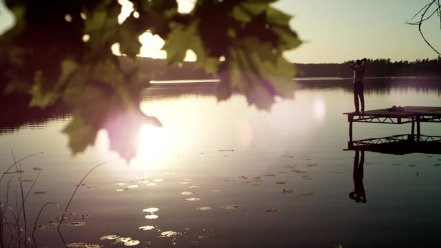 vídeos de stock e filmes b-roll de summer relaxation. admiring view from a lake pier - man admires forest