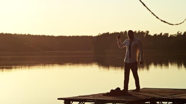 vídeos de stock e filmes b-roll de summer relaxation. businessman dancing on a lake pier - man admires forest