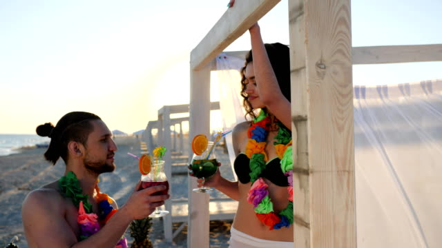 summer rest lovers guy and girlfriend on romantic trip, couple on vacation drinks cocktails and wearing flower hawaiian Lei video