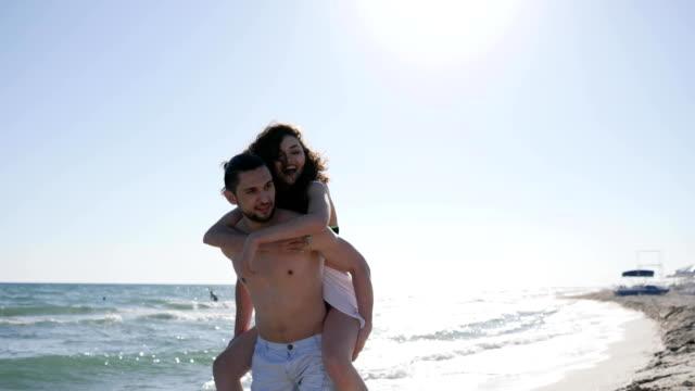 stockvideo's en b-roll-footage met rest van de zomer, vrolijk meisje springen op de kerel terug, achtergrondverlichting, paar op vakantie, wind ontwikkelt haar, tropen, oceaan kust - veleiding