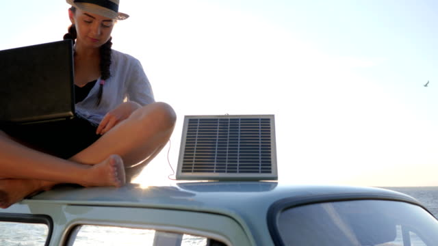 summer season, girl sits on roof car with solar array charges laptop and waving hello in backlight video