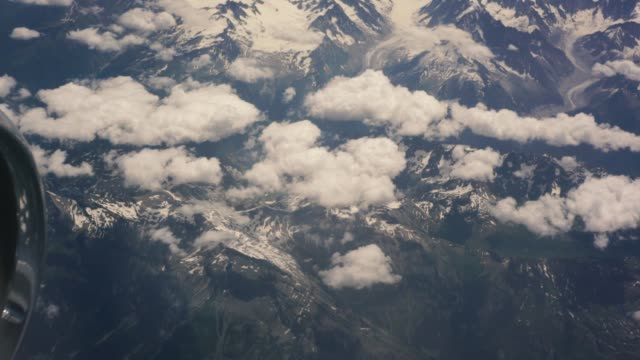 Summer snow-covered Alps view from the airplane window, the plane flies over the Alps mountains. Beautiful view from the porthole