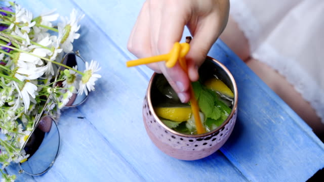 Summer table with refreshing drink Cold refreshing drink of lemon and mint in copper mug on blue table corner. Sunglasses and daisy flowers next to mug. Girl or woman sitting at the table mixing the drink. Top view. Close up mug stock videos & royalty-free footage