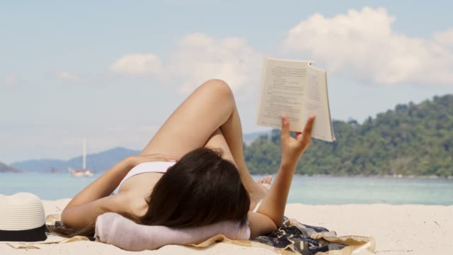 vídeos y material grabado en eventos de stock de vacaciones de verano asiático mujer leyendo un libro en la playa en tiempo libre vacaciones - acostado