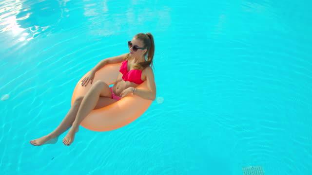 summer vacation woman i bikini på uppblåsbar madrass i poolen. överstsikt över flicka som njuter av att sola och njuta av resesemester vid resortpoolen. - inflatable ring bildbanksvideor och videomaterial från bakom kulisserna