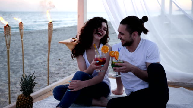 summer vacation, young people in love drink colorful cocktails with fruit, romantic couple on tropical beach video