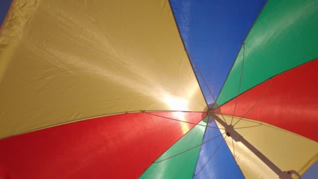 Summer vacations symbol: multi colored beach umbrella parasol protecting against the sun
