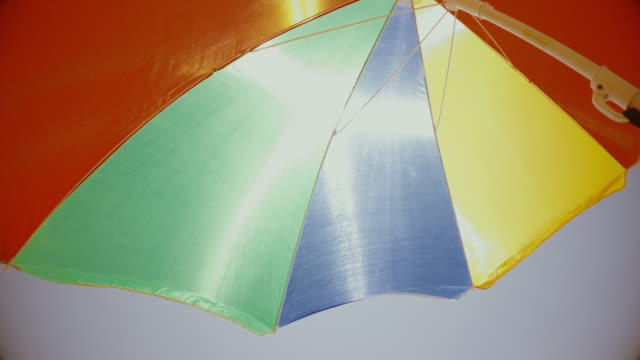 Summer vacations symbol: multi colored beach umbrella parasol protecting against the sun