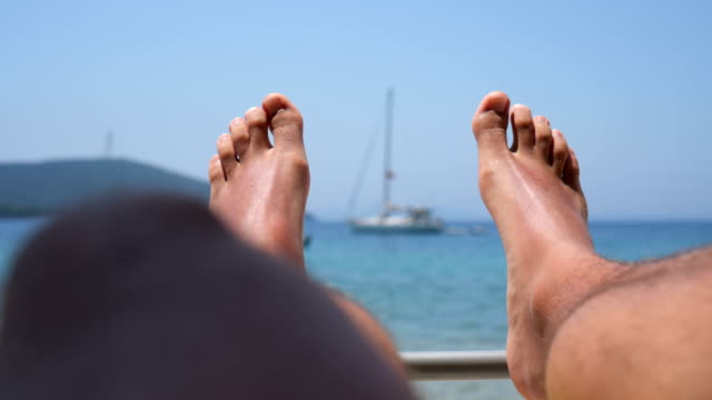 Summertime P.O.V of man relaxing on sunbed on the beach. lounge chair stock videos & royalty-free footage