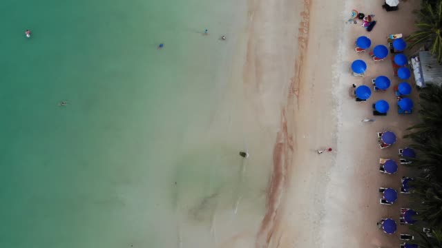 Sun beds on beach. Aerial view of many paired sun loungers with umbrella on deserted beach with clean sand.