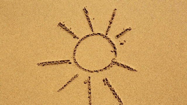 Sun drawn in the sand of a beach. full hd. summerfeeling video