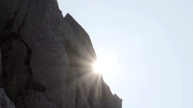 886d0e45311 Sun Emerging From Behind A Mountain Cliff Face video
