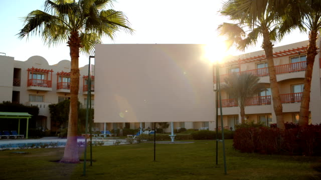 Sun flare behind a blank urban billboard video
