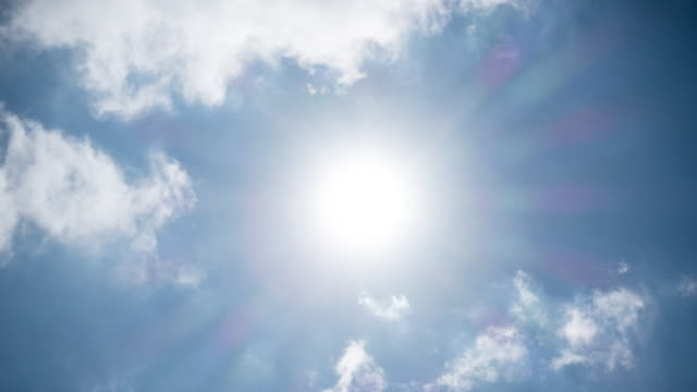 Sun in Blue Sky Time Lapse 4K time lapse video of bright sun in blue sky with clouds. summer background stock videos & royalty-free footage