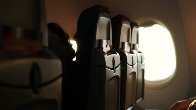 태양 비행기 창에서 빛나는 빛. 아름 다운 장면 조명과 승객 좌석 행의 실루엣 - airplane seat 스톡 비디오 및 b-롤 화면