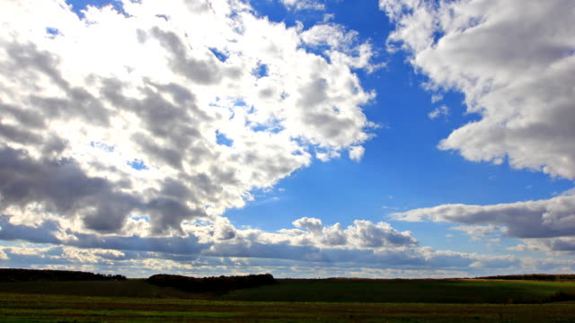 Sun rays, clouds flying on blue sky over field video