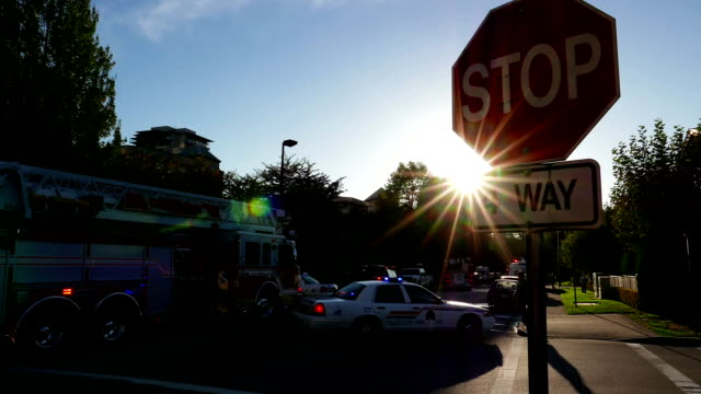Sun rays light shines through stop sign with fire accident scene video