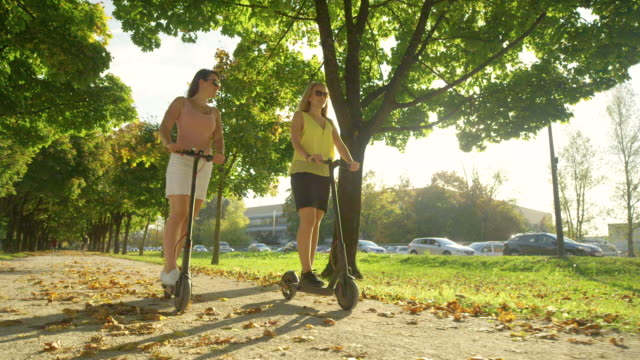 low angle: sun rays shine on friends riding electric scooters around the park - monopattino elettrico video stock e b–roll