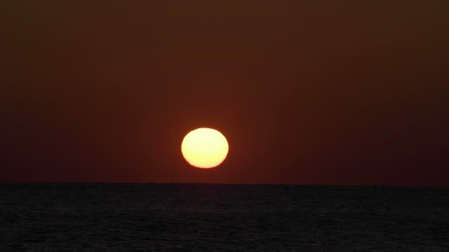 Sun Rises Over Water In Timelapse video