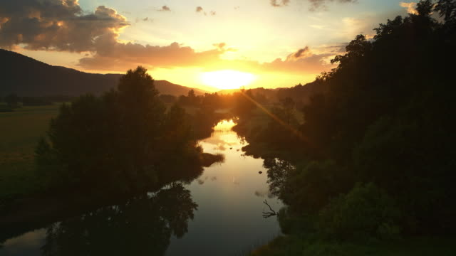AERIAL Sun rising above a river and surrounding meadows