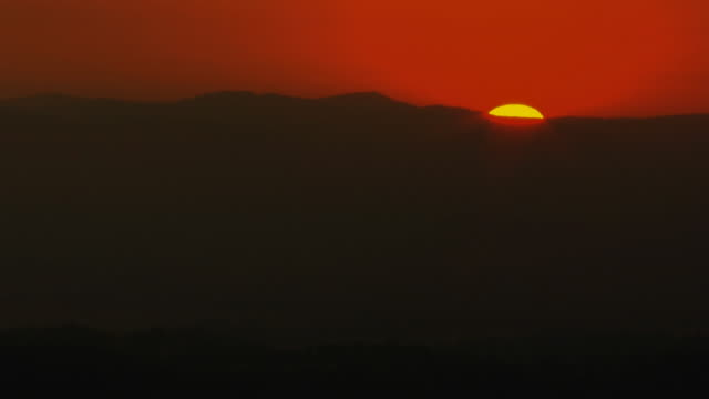 Sun Sets Behind Hill Timelapse of sun setting below a dark hill. 笹 stock videos & royalty-free footage