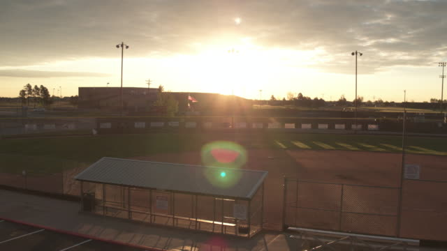 Sun Sets over a Baseball Field A stormy sunset casts its light over an empty baseball field at dusk. match sport stock videos & royalty-free footage