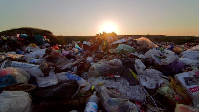 Sun setting over landfill site of domestic waste jib shot video
