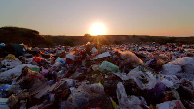 Sun setting over landfill site of domestic waste pan shot video