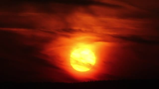 Sun setting through clouds, red sky video