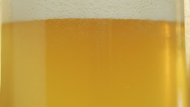 Sun shines through beer pouring into a glass, foam goes up Close-up shot. Sun shines through unfiltered beer pouring into a glass, bubbles rise and foam goes up Close-up shot. household fixture stock videos & royalty-free footage