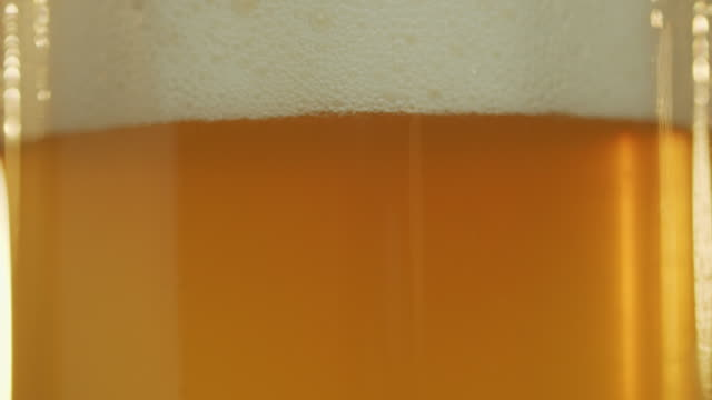 Sun shines through beer pouring into a glass, foam goes up. Close-up shot. Sun shines through unfiltered beer pouring into a glass, bubbles rise and foam goes up. Close-up shot. household fixture stock videos & royalty-free footage