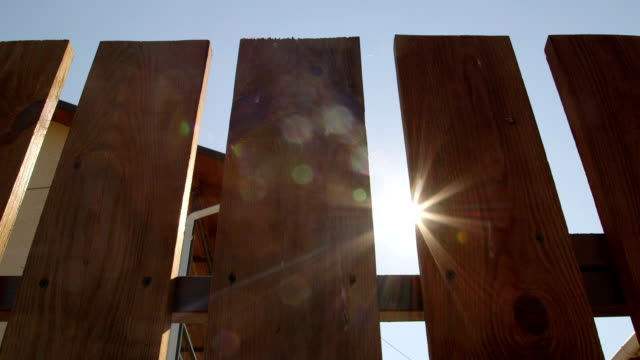 Sun shining through a new wooden fence around backyard dolly shot video