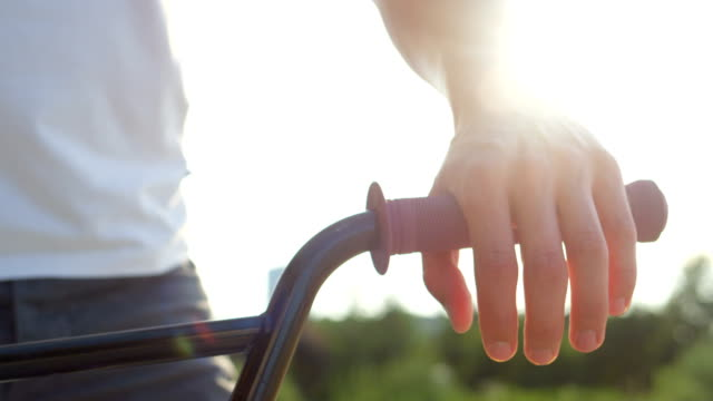 SLOW MOTION CLOSE UP: Sun shining through bmx biker placing hands on handlebar SLOW MOTION EXTREME CLOSE UP DOF: Details of bmx bike equipment, extreme biker placing hands on handlebar grips. Sun shining behind bmx biker holding bike handlebar, preparing to ride in city gripping stock videos & royalty-free footage