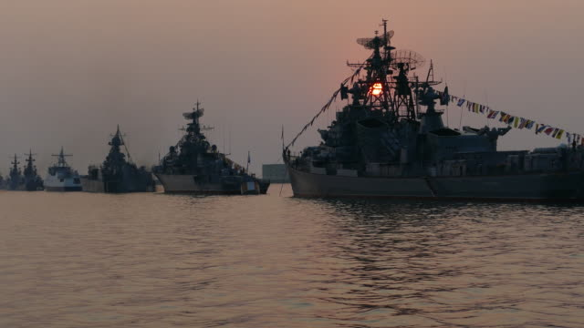 sun silhouettes warships at sunset video