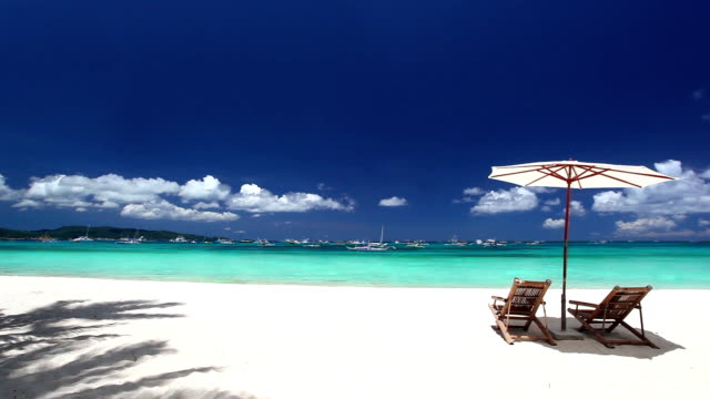 Sun umbrella and two beds on tropical beach video