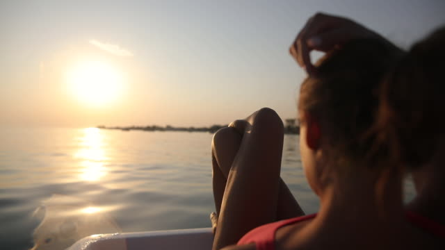 Sunbathing at sunset is best for tanning. Beautiful teenage girl relaxing on pedal boat Sunbathing at sunset is best for tanning. Beautiful teenage girl relaxing on pedal boat cross legged stock videos & royalty-free footage