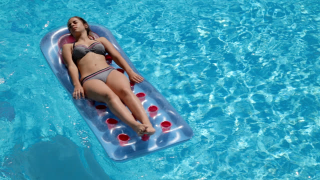 Sunbathing on pool raft video