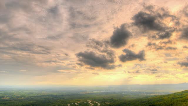 sunbeam with clouds moving over mountains and meadows. - dramatisk himmel bildbanksvideor och videomaterial från bakom kulisserna