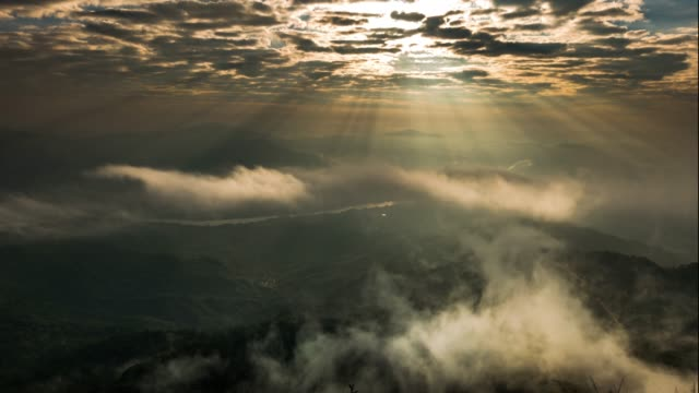 sunbeams and fog rolls across flowing over mountains - trees in mist stock videos & royalty-free footage